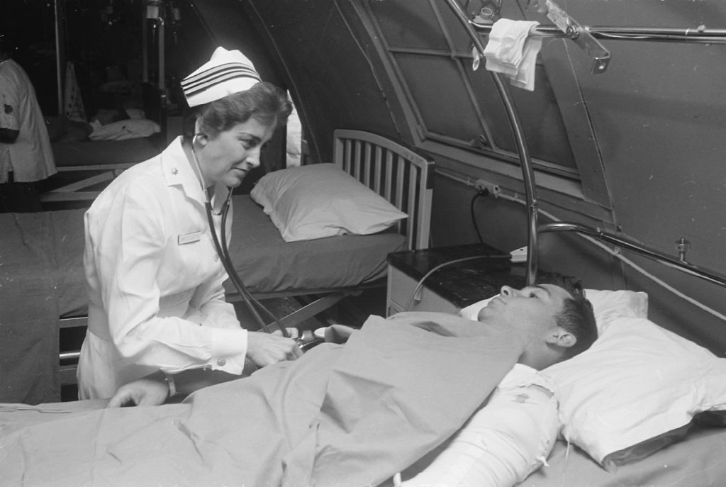 1920px-Da_Nang,_South_Vietnam...United_States_Navy_nurse_Lieutenant_Commander_Joan_Brouilette_checks_the_condition_of_Pfc...._-_NARA_-_558531